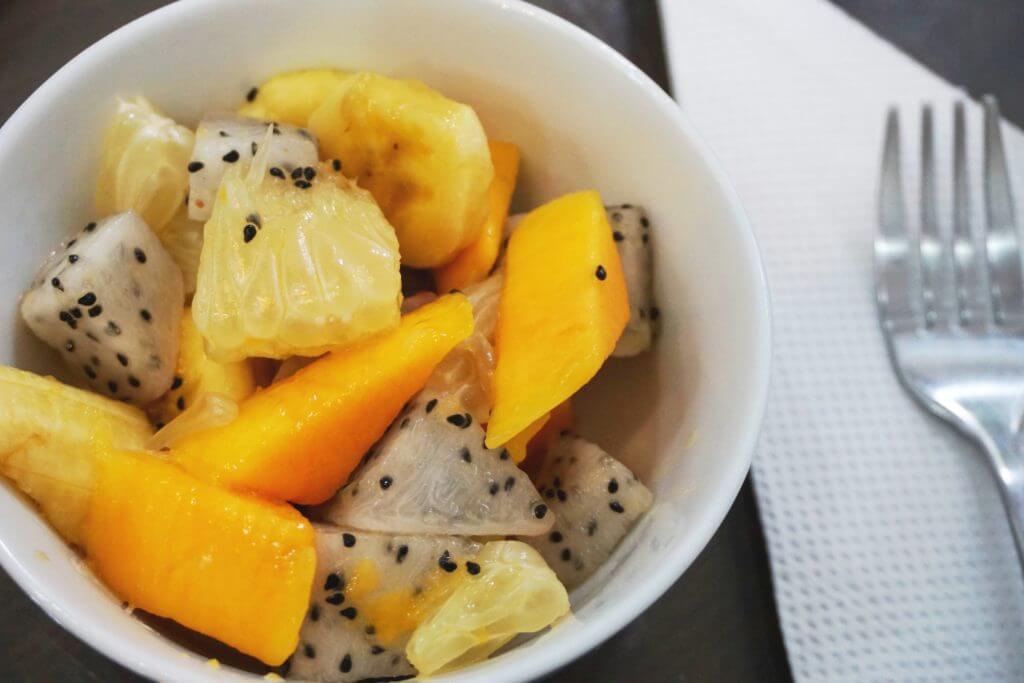 Fresh fruit salad in the morning, including black-speckled dragon fruit.